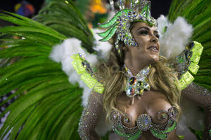 Photo - A performer from the Mocidade samba school parades during carnival celebrations at the Sambadrome in Rio de Janeiro, Brazil, Monday, March 3, 2014. Brazil's Carnival is maintaining its frenetic pace, with hundreds of roving parties taking over Rio de Janeiro's streets and famed samba school parades heading into their final night. (AP Photo/Felipe Dana)