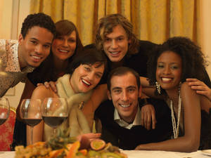 Photo - Portrait of Six Smiling Men and Women in Evening Wear Huddled Together at a Dining Table