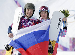 Photo - Russia's Vic Wild, left, poses after winning the gold medal in the men's snowboard parallel giant slalom final, with his wife and bronze medalist in the women's snowboard parallel giant slalom final, Russia's Alena Zavarzina, at the Rosa Khutor Extreme Park, at the 2014 Winter Olympics, Wednesday, Feb. 19, 2014, in Krasnaya Polyana, Russia.  (AP Photo/Andy Wong)
