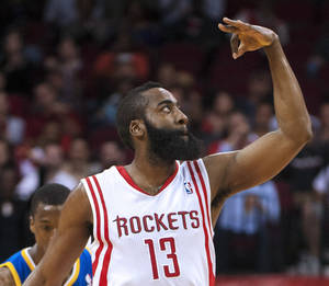 photo - Houston Rockets' James Harden signals to the crowd after shooting a 3-point basket during the first quarter of an NBA basketball game against the Golden State Warriors, Tuesday, Feb. 5, 2013, in Houston. (AP Photo/Dave Einsel)