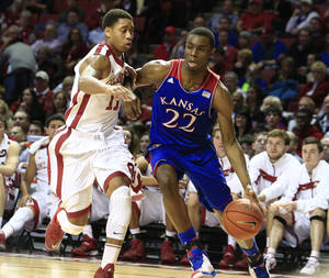 Photo - Kansas guard Andrew Wiggins, right, drives around Oklahoma guard Isaiah Cousins, left, during the first half of an NCAA college basketball game in Norman, Okla., Wednesday, Jan. 8, 2014. (AP Photo/Alonzo Adams)
