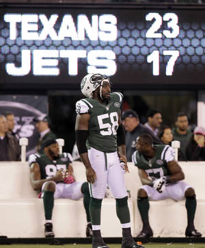 Photo -   In this photo taken Monday, Oct. 8, 2012, New York Jets' Bryan Thomas (58) and teammates Bart Scott (57) and Calvin Pace (97) watch from the sidelines late in the second half of their 23-17 loss to the Houston Texans in an NFL football game in East Rutherford, N.J. Some of the Jets' biggest flaws were on full display in their loss to the Texans. They couldn't run, the defense couldn't stop the run and Tebow still isn't getting on the field much. (AP Photo/Kathy Willens, File)