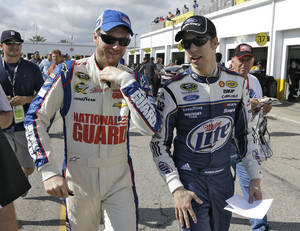 photo - Dale Earnhardt Jr., left, and Brad Keselowski walk through the garage area during a NASCAR Sprint Cup Series auto racing practice Saturday, Feb. 23, 2013, at the Daytona International Speedway in Daytona Beach, Fla. (AP Photo/Chris O'Meara)