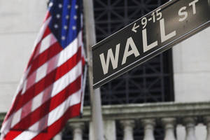 Photo - FILE - This Monday, July 15, 2013 file photo shows the American flag and Wall St. street sign outside the New York Stock Exchange, in New York. Asian stocks slumped Friday, June 27, 2014, after a reports showed weak U.S. consumer spending and slowing Chinese industrial profit growth, casting doubts on whether the world's two biggest economies can rebound. (AP Photo/Mark Lennihan, File)