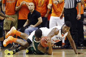Photo - Oklahoma State guard Marcus Smart, right, reaches for the ball over South Florida's Anthony Collins in the first half of an NCAA college basketball game in Stillwater, Okla., Wednesday, Dec. 5, 2012. (AP Photo/Sue Ogrocki)