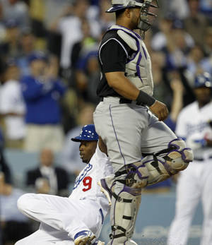 Photo - Los Angeles Dodgers' Dee Gordon (9) scores on a triple, and an error by Colorado Rockies left fielder Charlie Blackmon, without a throw to Rockies catcher Wilin Rosario, right, in the third inning of a baseball game on Monday, June 16, 2014, in Los Angeles.   (AP Photo/Alex Gallardo)