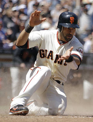 "photo - FILE - In this May 17, 2012, file photo, San Francisco Giants' Angel Pagan celebrates after scoring against the St. Louis Cardinals during a baseball game in San Francisco. San Francisco and free-agent center fielder Pagan agreed to a $40 million, four-year contract Monday, Dec. 3, 2012, as the winter meetings got under way in Nashville, Tenn. Bobby Evans, the team's vice president of baseball operations, said the deal with Pagan was ""very close"" and the leadoff hitter would be subject to a physical to finalize his return to the reigning World Series champions. (AP Photo/Ben Margot, File)"