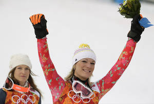 Photo - Women's supercombined gold medal winner Germany's Maria Hoefl-Riesch and bronze medal winner United States' Julia Mancuso celebrate after a flower ceremony at the Sochi 2014 Winter Olympics, Monday, Feb. 10, 2014, in Krasnaya Polyana, Russia. (AP Photo/Charles Krupa)