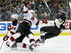 Photo - Pittsburgh Penguins' James Neal (18) and New Jersey Devils' Anton Volchenkov (28) collide during the second period of an NHL hockey game on Saturday, Feb. 2, 2013 in Pittsburgh. (AP Photo/Keith Srakocic)