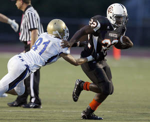 Photo - Putnam City's Denzel Dean slips past Choctaw's Ty Stayton during the high school football game between Putnam City and Choctaw at Putnam City High School in Oklahoma City, Thursday, Sept. 19, 2013. Photo by Sarah Phipps, The Oklahoman
