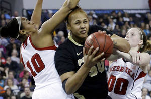 Photo - Purdue forward Taylor Manuel, center, drives to the basket against Nebraska forward Meghin Williams, left, and guard Lindsey Moore during the first half of an NCAA college basketball game in the Big Ten Conference tournament in Hoffman Estates, Ill., on Saturday, March 9, 2013. (AP Photo/Nam Y. Huh)