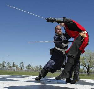 Photo - Mark McCarthy, left, and Tim McCoy joust at a dress rehearsal for the Medieval Fair, which opens Friday.