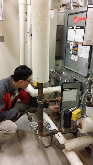 Photo -  OU researcher Ikseong Joo checks sensor connections in an air handling unit that is part of a system designed to help heating and air conditioning systems run more efficiently.  <strong> -   </strong>