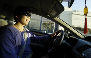 photo - In this Jan. 4, 2013 photo, Lyft driver Nancy Tcheou smiles as she drives in San Francisco. Fed up with traditional taxis, city dwellers are tapping their smartphones to hitch rides from strangers using mobile apps that allow riders and drivers to find each other. Internet-enabled ridesharing services such as Lyft, Uber and Sidecar are expanding rapidly in San Francisco, New York and other U.S. cities, billing themselves as a high-tech, low-cost alternative to cabs. (AP Photo/Jeff Chiu)