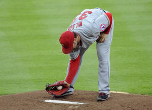 Photo - Los Angeles Angels starter C.J. Wilson dusts off the pitcher's mound after giving the Atlanta Braves back-to-back home runs during the first inning of a baseball game on Friday, June 13, 2014, in Atlanta. (AP Photo/David Tulis)