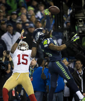 Photo - CORRECTS BYLINE TO PAUL KITAGAKI JR.-Seattle Seahawks cornerback Richard Sherman (25) hits the ball away from San Francisco 49ers wide receiver Michael Crabtree (15) and is intercepted by Seattle Seahawks outside linebacker Malcolm Smith (53) during the NFL football NFC Championship game, Sunday, Jan. 19, 2014, in Seattle. The Seahawks won 23-17 to advance to the Super Bowl. (AP Photo/The Sacramento Bee, Paul Kitagaki Jr.) MAGS OUT; TV OUT (KCRA3, KXTV10, KOVR13, KUVS19, KMAZ31, KTXL40) MANDATORY CREDIT