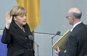 Photo - German Chancellor Angela Merkel, left, takes the oath of office by President of the Federal Parliament, Norbert Lammert during a meeting of the German federal parliament, Bundestag, in Berlin, Germany, Tuesday, Dec. 17, 2013. (AP Photo/Jens Meyer)