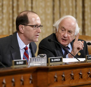 """Photo - House Ways and Means Committee Chairman Rep. Dave Camp , R-Mich., left, and the committee's ranking member, Rep. Sander Levin, D-Mich., exchange words on Capitol hill in Washington, Wednesday, April 9, 2014, during a disagreement over procedure as the panel debates whether IRS official Lois Lerner's refusal to testify to Congress deserves criminal prosecution. After Rep. Levin's insistence that he, the top Democrat, be heard, Chairman Camp told Levin to """"chill out."""" Levin replied that he was """"very chilled out."""" Ways and Means wants the Justice Department to open a criminal probe against Lerner. (AP Photo/J. Scott Applewhite)"""