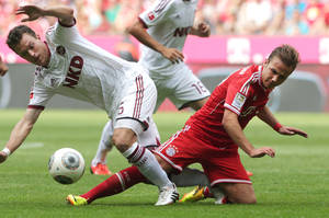 Photo - Nuremberg's Niklas Stark, left, and Bayern's Mario Goetze challenge for the ball during the German first division Bundesliga soccer match between FC Bayern Munich and 1. FC Nuremberg, in Munich, southern Germany, Saturday, Aug. 24, 2013. (AP Photo/Matthias Schrader)
