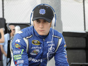 Photo - FILE - In this April 11, 2014 file photo, Cole Whitt waits before qualifying for a NASCAR Sprint Cup series auto race at Darlington Speedway in Darlington, S.C. Swan Racing's future is on the rocks and the two-car team is reviewing its ability to compete in NASCAR. Whitt drives the No. 26 Toyota Camry and Parker Kligerman drives the No. 30 Toyota Camry for Swan in the Sprint Cup series. Swan Racing is owned by Brandon Davis, the CEO of independent oil and gas company Swan Energy.   (AP Photo/Mike McCarn, File)