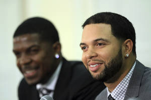Photo -   Deron Williams, right, and Joe Johnson smile during a news conference to introduce the Brooklyn Nets new backcourt of All-Stars at Brooklyn Borough Hall, Friday, July 13, 2012, in the Brooklyn borough of New York. The Nets re-signed Williams and acquired Joe Johnson, seated left. (AP Photo/Mary Altaffer)