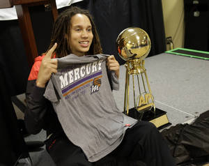 Photo - Baylor's Brittney Griner holds up Phoenix Mercury shirt as she poses next to The Associated Press College Basketball Player of the Year trophy during a news conference at the Women's Final Four of the NCAA college basketball tournament, Saturday, April 6, 2013, in New Orleans. (AP Photo/Gerald Herbert)
