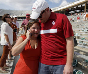 Photo - Lydia Crawford and Clayton Kelley hug after Kelley asked Crawford to marry him after the Red River Rivalry college football game between the University of Oklahoma Sooners (OU) and the University of Texas Longhorns (UT) at the Cotton Bowl in Dallas, Saturday, Oct. 8, 2011. Photo by Bryan Terry, The Oklahoman