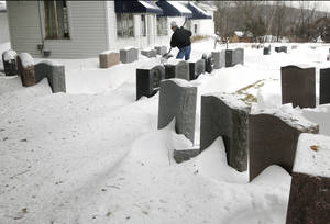 Photo - Rick Atwood clears memorial stones at Atwood Memorial Company in Haverhill, Mass. Monday, Feb. 11, 2013. Beleaguered Massachusetts residents returned to work on Monday for the first time since the weekend blizzard, crawling along narrow snow-covered secondary roads and being greeted by a new wintry mix of sleet and freezing rain. (AP Photo/Elise Amendola)