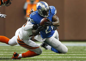 Photo - Detroit Lions running back Reggie Bush (21) is brought down by Cincinnati Bengals free safety Reggie Nelson (20) in the first quarter of an NFL football game Sunday, Oct. 20, 2013, in Detroit. (AP Photo/Rick Osentoski)