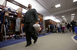 Photo - New England Patriots rookie free-agent, defensive tackle Joe Vellano,  walks past quarterback Tom Brady's locker carrying an autographed team ball and a helmet at the NFL football team's facility in Foxborough, Mass., Monday, Jan. 20, 2014. The Patriots lost to the Denver Broncos in the AFC Championship game Sunday in Denver ending their season. (AP Photo/Stephan Savoia)
