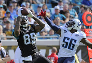 Photo - Jacksonville Jaguars tight end Marcedes Lewis (89) makes a reception in front of Tennessee Titans outside linebacker Akeem Ayers (56) during the first half of an NFL football game in Jacksonville, Fla., Sunday, Dec. 22, 2013. (AP Photo/Stephen Morton)
