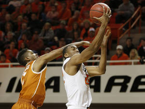 Photo - Oklahoma State wing Markel Brown (22) shoots in front of Texas guard Isaiah Taylor (1) during the second half of an NCAA college basketball game in Stillwater, Okla., Wednesday, Jan. 8, 2014. Oklahoma State won 87-74. (AP Photo/Sue Ogrocki)