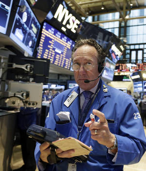 Photo - Trader Steven Kaplan works on the floor of the New York Stock Exchange Wednesday, March 12, 2014. Asian stock markets vacillated Thursday March 27, 2014 as investors waited to see if weak Chinese economic data might prompt new economic stimulus. European shares drifted down.  (AP Photo/Richard Drew)