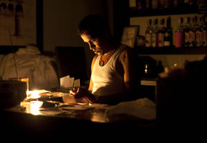 Photo -   A bartender works on accounts by candle light during the blackout in Havana, Cuba, Sunday, Sept 9, 2012. Power failed across a large swath of western Cuba on Sunday night, including the capital, Havana, and the popular tourist resort of Varadero, plunging millions of people into darkness. (AP Photo/Ramon Espinosa)
