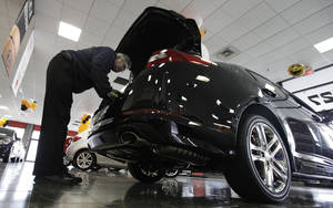 Photo - FILE - In this Oct. 5, 2012 file photo, a shopper checks out a Kia Optima at a Kia car dealership in Elmhurst, Ill. Auto Web sites _ once filled mostly with reviews and advice _ are getting more sophisticated, connecting potential buyers with dealers and offering instant price guarantees. (AP Photo/Nam Y. Huh, File)