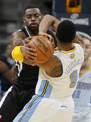 Photo - Sacramento Kings guard Tyreke Evans, left, tries to steal the ball from Denver Nuggets guard Andre Iguodala during the first quarter of an NBA basketball game in Denver on Saturday, Jan. 26, 2013. (AP Photo/David Zalubowski)