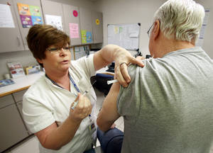 Photo - Registered nurse D.J. Gentry gives a patient a flu vaccine Jan. 4 at the Cleveland County Health Department in Norman. PHOTO BY STEVE SISNEY, THE OKLAHOMAN
