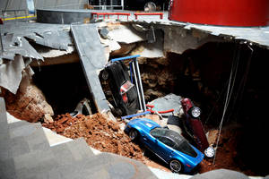 Photo - In this Wednesday, Feb. 12, 2014 photo, cars lie in a sinkhole that opened up at the Skydome showroom in the National Corvette Museum in Bowling Green, Ky. The sinkhole that swallowed eight cars at the has become such an attraction that officials want to preserve it. They may even put one or two of the cars back inside the hole. The board of the museum in Kentucky voted Wednesday, June 25, 2014 to preserve a large section of the sinkhole that opened beneath the museum in February. (AP Photo/Michael Noble Jr.)
