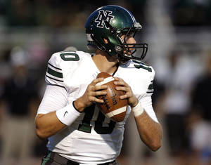 Photo - Norman North's David Cornwell looks to throw a pass during a high school football game between Yukon and Norman North in Yukon, Okla.,   Friday, Oct. 4, 2013. Photo by Sarah Phipps, The Oklahoman