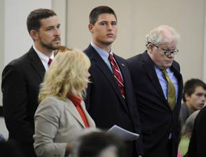 Photo - Former Vanderbilt football player Brandon Vandenburg, center, stands with his attorneys Nathan Colburn, left, and David King, right, during a discussion hearing at the Birch Building Wednesday, Oct. 16, 2013 in Nashville, Tenn. Attorneys set a trial date of Aug. 11 on Wednesday for Vandenburg, of Indio, Calif., and Cory Batey, of Nashville, two former Vanderbilt football players charged with raping an unconscious fellow student. Two other ex-players, Brandon Banks, of Brandywine, Md., and Tip McKenzie, of Woodville, Miss., are also charged with rape in the June 23 incident. Their cases were separated from the other two players on Wednesday.  (AP Photo/The Tennessean, Sanford Myers)
