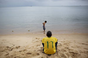 Photo - Paulo Cesar Da Silva, wearing his Brazilian soccer T-shirt with a weathered #10, the number associated with soccer star Neymar, looks out to the ocean as his son Gabriel wades along the shoreline in Fortaleza, Brazil, Thursday, July 3, 2014. For two whole days now, the globe has gone without World Cup soccer matches in this most electrifying of tournaments in decades. There were no matches on Wednesday and Thursday as teams still standing took a break before heading into Friday's quarterfinal matches. (AP Photo/Rodrigo Abd)
