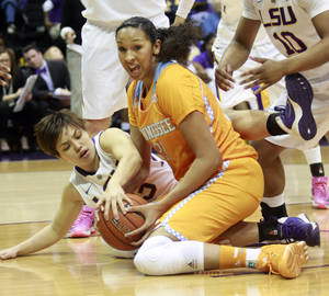Photo - LSU guard Rina Hill, left, fights Tennessee center Mercedes Russell (21) for a loose ball in the first half of an NCAA college basketball game in Baton Rouge, La., Thursday, Feb. 27, 2014. (AP Photo/Tim Mueller)
