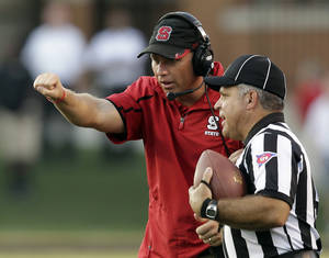 Photo - North Carolina State head coach Dave Doeren, left, argues a call with a referee in the second half of an NCAA college football game against Wake Forest in Winston-Salem, N.C., Saturday, Oct. 5, 2013. Wake Forest won 28-13. (AP Photo/Chuck Burton)