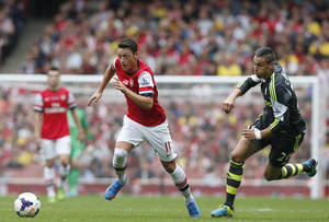 Photo - Arsenal's Mesut Ozil, left, takes the ball away from the chasing Stoke City's Geoff Caneron during the English Premier League soccer match between Arsenal and Stoke City at Emirates Stadium in London, Sunday, Sept. 22, 2013. (AP Photo/Sang Tan)