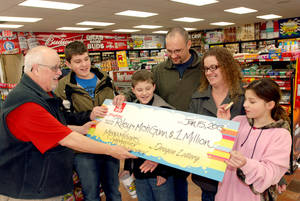 Photo - The Gunn family of Wolf Creek, Ore., accepts a symbolic check for $1 million before taxes from Oregon Lottery official Ray Martin on Tuesday, Jan. 15, 2013, at the convenience store where they bought it in Merlin, Ore. Riley Gunn lost his job as a project manager for a telecommunications company in May 2012 and moved his family to a one-room cabin outside Wolf Creek, Ore. While he and his wife were driving home, they pulled off the freeway for corn dogs and pizza pockets and bought an $8 ticket, and won $1 million dollars. Riley and Misti Gunn are at center, with their sons Elijah, 13, left, and Isac, 11, and daughter, Destenie, 9, right. (AP Photo/Jeff Barnard)