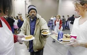 Photo - A man is offered pumpkin pie by volunteers during the 2008 Red Andrews Christmas Dinner. Photo BY JIM BECKEL, THE OKLAHOMAN