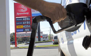 Photo - FILE-In this Tuesday, Aug. 28, 2012, file photo, a  man pumps gas into his van while a sign advertises that a gallon of regular unleaded costs $4.09 at the Speedway on South Westnedge Avenue in Kalamazoo, Mich. Drivers are facing the biggest one-day jump in gasoline prices in 18 months, Wednesday, Aug. 29, 2012, as Hurricane Isaac swamps the nation's oil and gas hub along the Gulf Coast. The nationwide average for a gallon of regular gas rose a nickel Wednesday to $3.80 as refineries shut down or cut back to protect against Isaac's high winds and heavy rain. (AP Photo/Kalamazoo Gazette, Mark Bugnaski) ORG XMIT: MIKAL201