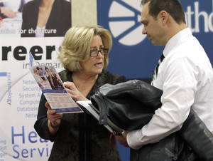Photo - FILE - In this Wednesday, Jan. 22, 2014 file photo, recruiter Valera Kulow, left, speaks with job seeker Leonardo Vitiello during a career fair in Dallas. The Labor Department's job openings and labor turnover survey for February is released on Tuesday, April 8, 2014. (AP Photo/LM Otero, File)