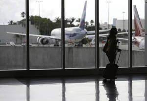 Photo -   FILE-In this Thursday, Sept. 27, 2012, file photo, a passenger walks through the south terminal at Miami International Airport in Miami. U.S. companies are continuing to cut back on employee travel plans amid uncertainty surrounding the health of the economy. Americans are expected to take 438.1 million business trips this year, down 2 percent from last year, the Global Business Travel Association said Tuesday, Oct. 9, 2012. (AP Photo/Lynne Sladky)