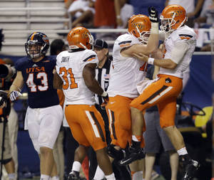 Photo - Oklahoma State's J.W. Walsh, right, celebrates with teammates after he score on a run against Texas San Antonio during the first half of an NCAA college football game, Saturday,  Sept. 7, 2013, in San Antonio. Oklahoma State won 56-35.(AP Photo/Eric Gay)